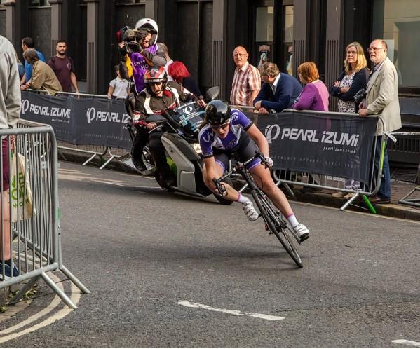 alan-rolfe-pearl-izumi-rider-speeding-around-bend-with-press-on-bike